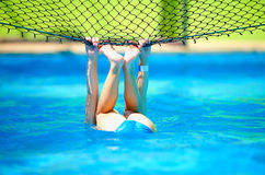 Gullig pojkeunge som har gyckel som gör jippo på volleyboll netto i pöl Royaltyfri Bild