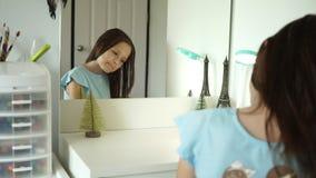 Gullig preteen flicka som ser i spegeln och kammar hennes hår arkivfilmer