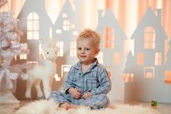 Gullig pys för blont hår i sleepwear nära hus för julleksakpapper royaltyfri bild