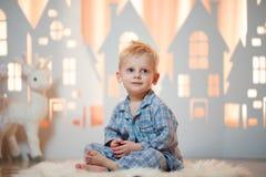 Gullig pys för blont hår i sleepwear nära hus för julleksakpapper royaltyfria bilder