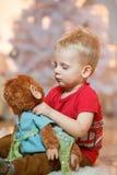 Gullig pys för blont hår med hans favorit- leksak royaltyfri fotografi