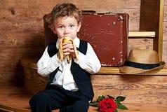 Gullig pys med en banan i hans handsitting Arkivbilder