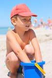 Gullig pys med en hink på stranden royaltyfri bild