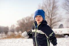 Gullig pys med en kasta snöboll Arkivbilder