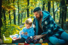 Gullig pys med hans fader under promenad i skogfadern som spelar med den lilla sonen på en picknick i parkera in royaltyfri fotografi