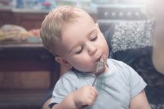 Gullig pys med nöje som för första gången äter en sallad i hans livsammanträde på händer för mamma` s arkivbild