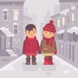 Gullig pys och flicka som tillsammans går i en snöig vinterstad Royaltyfri Fotografi