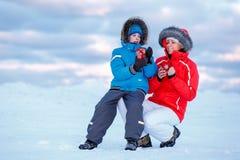 Gullig pys och hans moder som dricker varmt te på den iskalla stranden Royaltyfri Fotografi