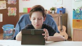 Gullig pys som använder den digitala minnestavlan som bläddrar internet lager videofilmer