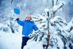 Gullig pys som bär varm kläder som spelar på vinterskog Royaltyfri Bild