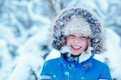 Gullig pys som bär varm kläder som spelar på vinterskog Royaltyfri Foto