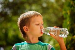 Gullig pys som dricker mineralvatten från den plast- flaskan I Royaltyfria Bilder