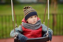 Gullig pys som har gyckel på utomhus- lekplats Barn på gunga arkivbild