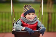 Gullig pys som har gyckel på utomhus- lekplats Barn på gunga royaltyfri bild