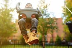 Gullig pys som har gyckel på utomhus- lekplats Barn på gunga arkivfoto