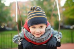 Gullig pys som har gyckel på utomhus- lekplats Barn på gunga fotografering för bildbyråer