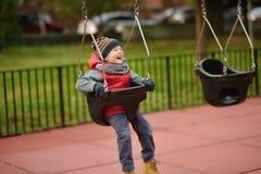 Gullig pys som har gyckel på utomhus- lekplats Barn på gunga royaltyfria bilder