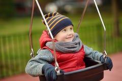 Gullig pys som har gyckel på utomhus- lekplats Barn på gunga arkivbilder