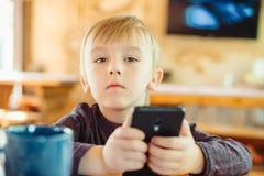 Gullig pys som hemma spelar lekar på smartphonen royaltyfri fotografi
