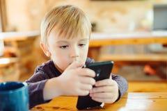 Gullig pys som hemma spelar lekar på smartphonen royaltyfri bild