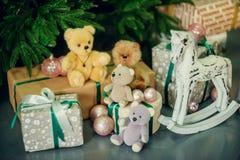 Gullig pys som ner sitter vid den dekorerade julgranen med leksaker, nallebjörnar och gåvaaskar royaltyfria bilder