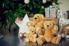 Gullig pys som ner sitter vid den dekorerade julgranen med leksaker, nallebjörnar och gåvaaskar royaltyfri foto