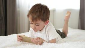 Gullig pys som spelar genom att använda smartphonen Applikationer för utvecklingen av barn stock video
