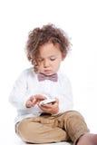 Gullig pys som spelar med en mobiltelefon Arkivfoton