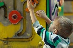 Gullig pys som spelar med leksaker på lekplats Arkivbilder