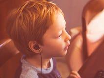 Gullig pys som spelar på datoren med hörlurar med mikrofon royaltyfria foton