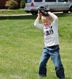 Gullig pys som täcker hans huvud med baseballhandsken arkivbilder