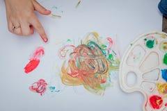 Gullig pysmålning med en målarfärg räcker genom att använda ofina målarfärger Arkivbild