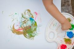 Gullig pysmålning med en målarfärg räcker genom att använda ofina målarfärger Royaltyfri Fotografi