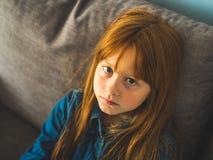 Gullig rödhårig manliten flicka som ser oss som är allvarliga royaltyfri foto