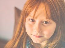 Gullig rödhårig manliten flicka som ser oss och att le arkivfoton