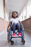 Gullig rörelsehindrad elev som ler på kameran i korridor royaltyfria bilder