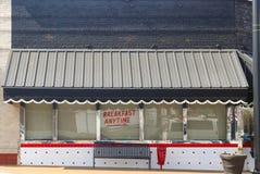 Gullig retro matställe med markisen med kammusslor ovanför reflekterande trafik för fönster och frukosten som visas när som helst arkivbild