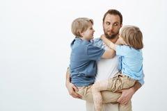 Gullig rolig caucasian fader som rymmer två unga söner i armar, stirrar på mer ung pojke och gör framsidor och att vara positivt  Arkivbilder