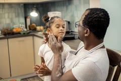 Gullig rolig dotter som har hennes framsida i mjöl, når att ha bakat pajen arkivfoto