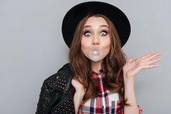 Gullig rolig flicka i hatt som tuggar bubbelgum Fotografering för Bildbyråer