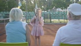 Gullig rolig flicka med två råttsvansar som står på tennisbanan som rymmer racket som överför luftkyssar till farmodern och arkivfilmer