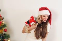 Gullig rolig kvinna i jultomtenhatt med leksakterriern nära jul tr Royaltyfri Bild