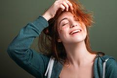 Gullig rolig lycka för ung kvinna som rör till hår royaltyfria foton