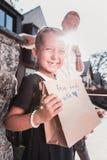 Gullig rolig svartögd dotter som ler mening i huvudsak lyckligt på födelsedag royaltyfria foton