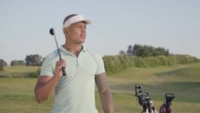 Gullig säker lyckad mitt för stående - östlig man med ett golfklubbanseende på en golfbana i bra soligt väder lager videofilmer