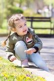 Gullig söt liten flicka som på våren sitter gräs med tusenskönor Royaltyfri Fotografi