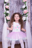 Gullig söt liten flicka som svänger på en vagga med blommor Royaltyfri Foto