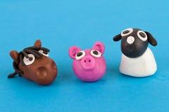 Gullig samling för plasticinelantgårddjur - svin, häst, får Arkivfoto