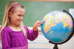Gullig schoolgirl som pekar på ett land Royaltyfri Bild