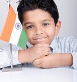 Gullig seende indisk unge med den indiska flaggan Royaltyfri Fotografi